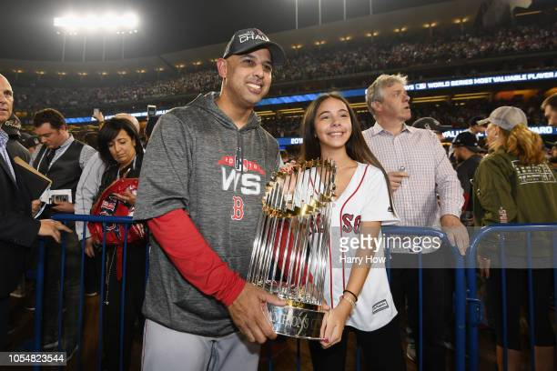 Manager Alex Cora of the Boston Red Sox celebrates with his daughter Camila and the World Series trophy after his team's 51 win over the Los Angeles...