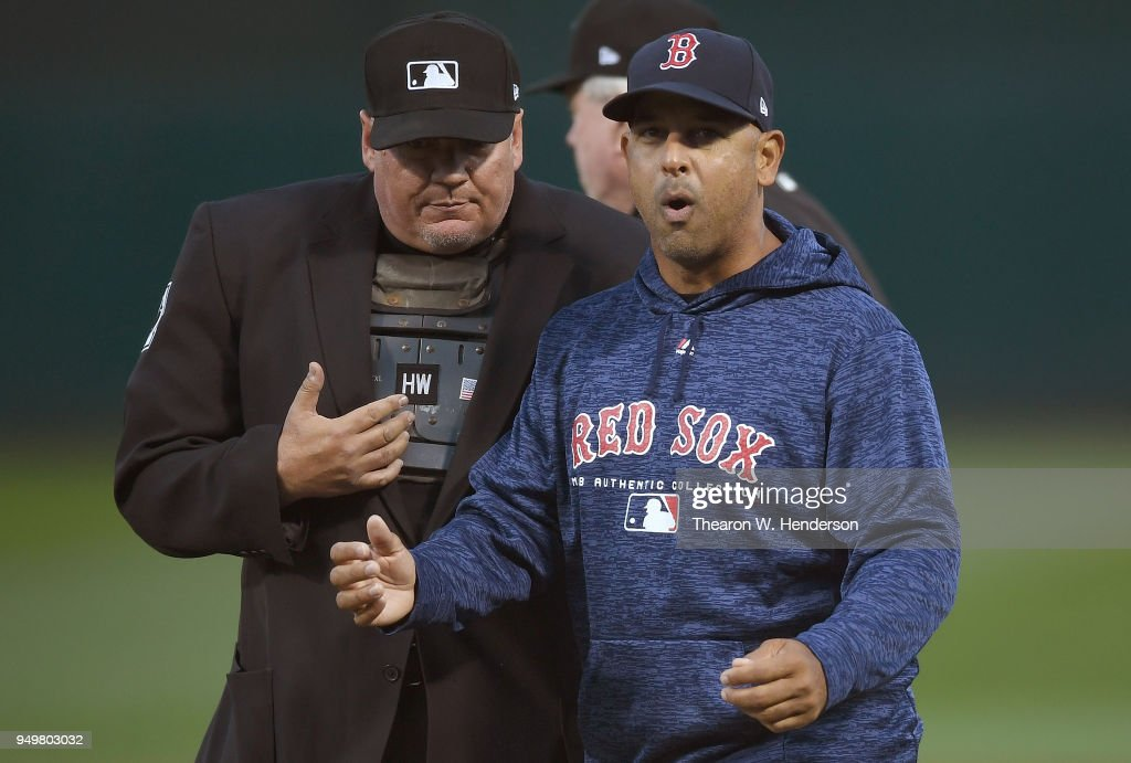 Manager Alex Cora #20 of the Boston Red Sox complains to home plate umpire Hunter Wendelstedt #21 after Wendelstedt changed a call on a Boston runner from safe to out in the top of the six inning against the Oakland Athletics at the Oakland Alameda Coliseum on April 21, 2018 in Oakland, California. Wendelstedt convered with the umpiring crew and a call from safe to out was made on base runner Andrew Benintendi #16.