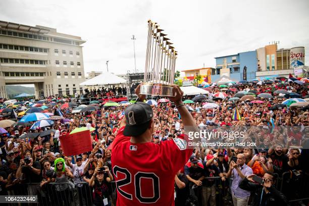Manager Alex Cora of the Boston Red Sox displays the 2018 World Series trophy during a World Series parade during a Boston Red Sox trip from Boston...