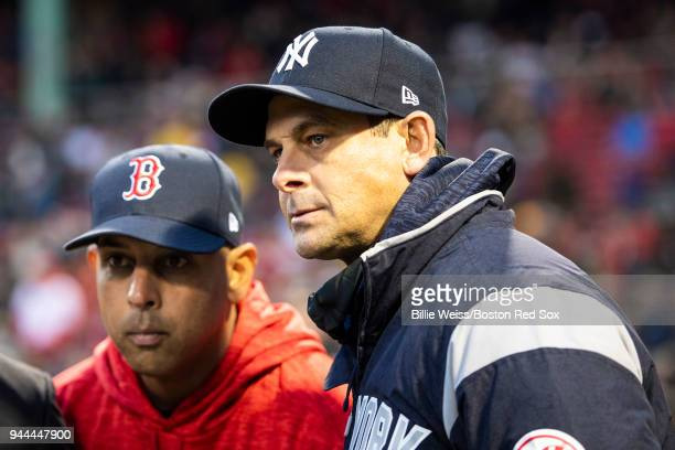 Manager Alex Cora of the Boston Red Sox looks on with manager Aaron Boone of the New York Yankees before a game on April 10 2018 at Fenway Park in...
