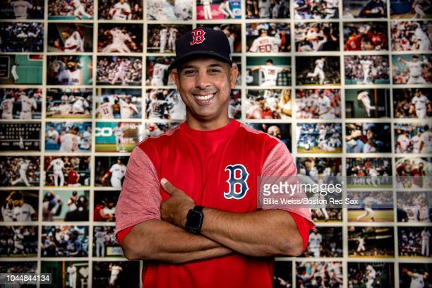Manager Alex Cora of the Boston Red Sox poses for a portrait in front of a wall of photographs depicting every win throughout the season in his...