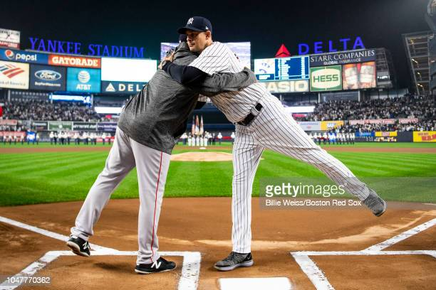 Manager Alex Cora of the Boston Red Sox shakes hands with Manager Aaron Boone of the New York Yankees before game three of the American League...