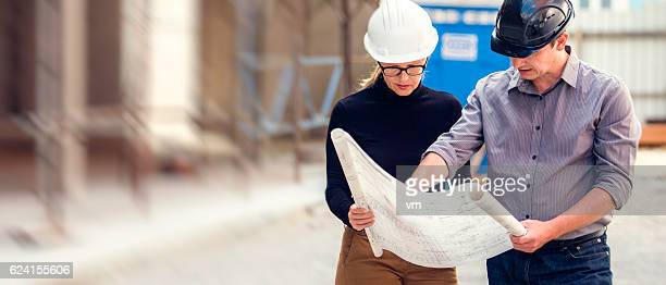 Manager and architect reviewing blueprints at a construction site