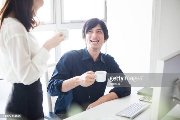 マネージャーとデザイナーがコーヒーを飲みながらチャット - 休憩中 ストックフォトと画像