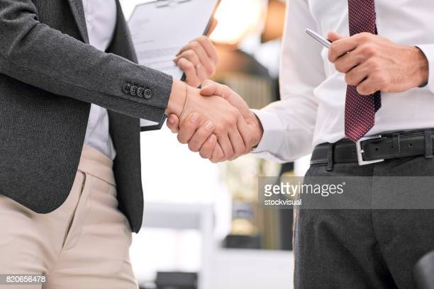 Manager and employee handshake in office