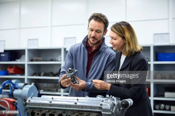 マネージャーとエンジニアは車の部品を議論します。