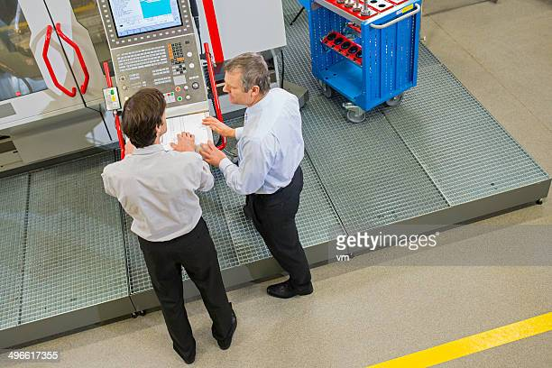 Manager and Engineer in the Factory Disscusing Project