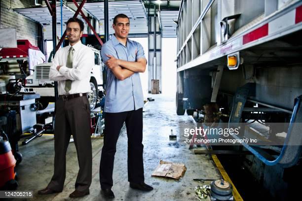 manager and mechanic standing in auto repair shop - potomac maryland - fotografias e filmes do acervo