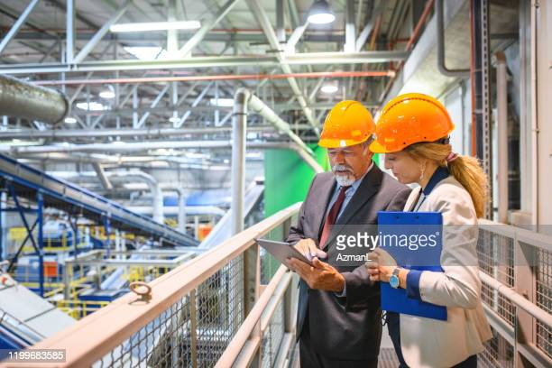 manager and quality controller inside recycling facility - waste management stock pictures, royalty-free photos & images