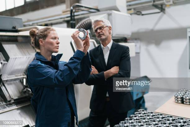 manager and skilled worker in high tech enterprise, checking machine parts - industriebetrieb stock-fotos und bilder