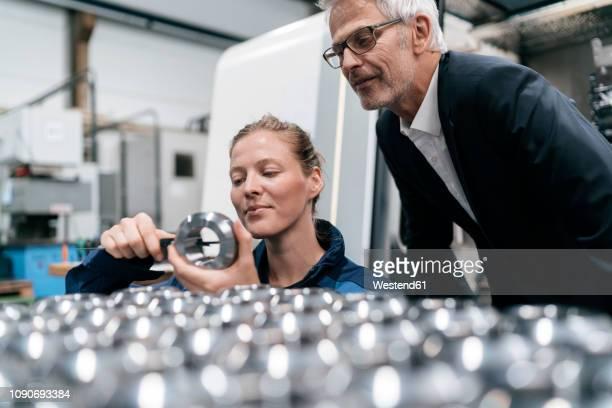 manager and skilled worker in high tech enterprise, checking machine parts - genauigkeit stock-fotos und bilder