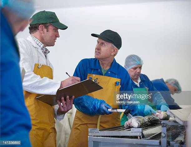 Manager and staff in discussion on production line of hand-reared Scottish salmon farm