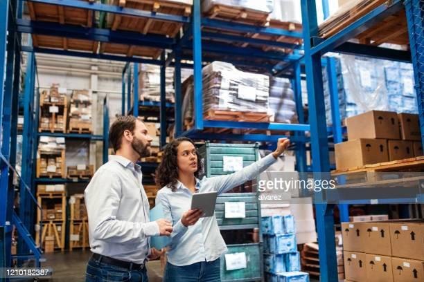 manager e supervisore che prendono l'inventario in magazzino - dirigente foto e immagini stock
