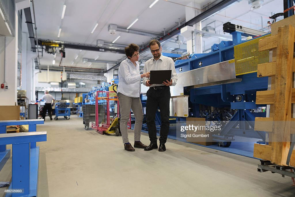 Manager and work colleague checking information on laptop : Stock-Foto