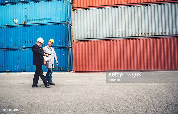 Manager And Worker Discussing While Walking At Commercial Dock