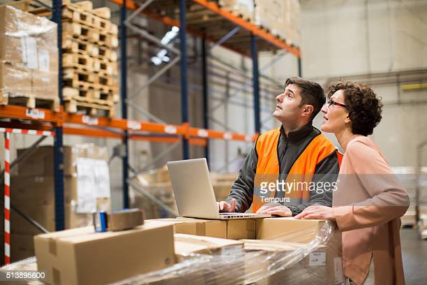 Manager and worker doing a checklist in the warehouse.