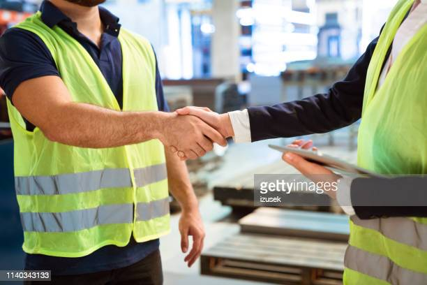 Manager and worker greeting each other in factory