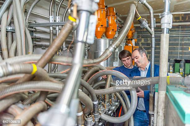 Manager and worker having work meeting in plastics factory