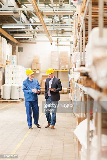 Manager and worker in warehouse with hard hats