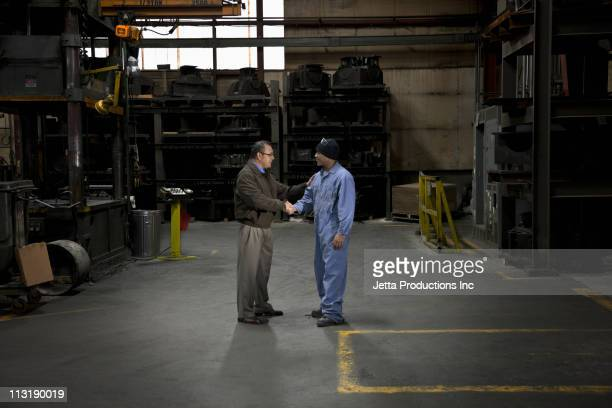Manager and worker shaking hands in factory