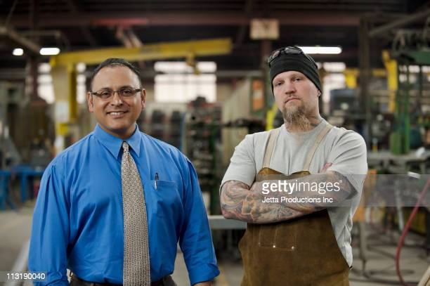 manager and worker standing in factory - contrasts stock pictures, royalty-free photos & images