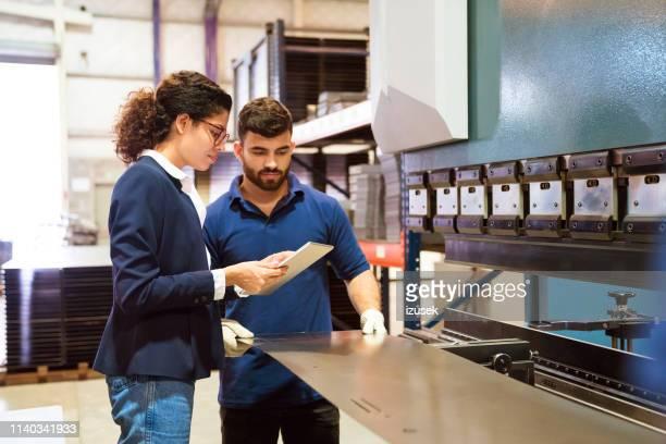 gerente y trabajador trabajando en fábrica - izusek fotografías e imágenes de stock