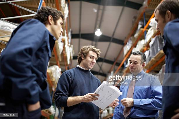 Manager and workers in warehouse