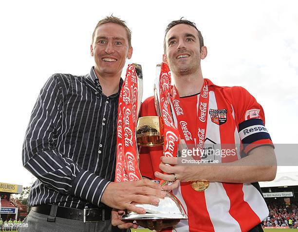 Manager Andy Scott and captain Kevin O'Connor of Brentford celebrate winning League Two with the Trophy during the CocaCola League Two match between...