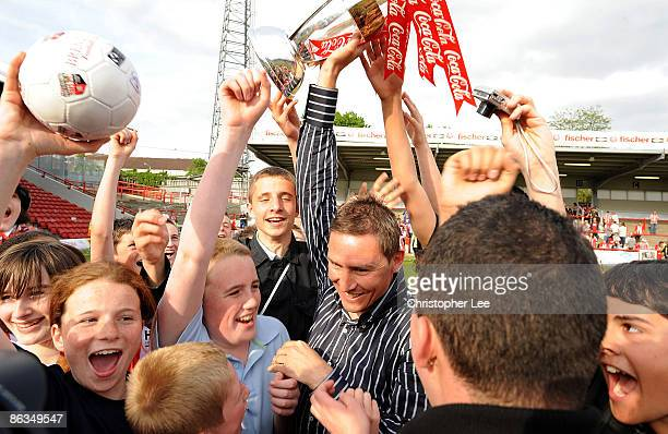 Manager Andy Scott of Brentford is mobbed by fans as he celebrates winning the League Two Championship during the CocaCola League Two match between...