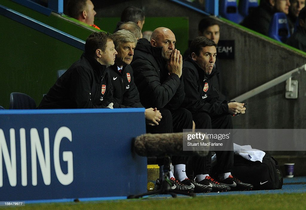 Manager Arsene Wenger (2nd L) of Arsenal sits alongside assistant Steve Bould (2nd R) during the Barclays Premier League match between Reading and Arsenal at Madejski Stadium on December 17, 2012 in Reading, England.