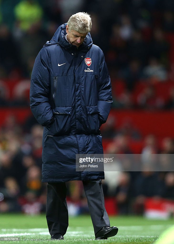 Manager Arsene Wenger of Arsenal watches from the touchline during the Barclays Premier League Match between Manchester United and Arsenal at Old Trafford on November 10, 2013 in Manchester, England.