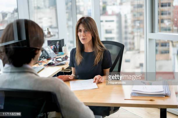 hr manager at her office talking to employee cheerfully - director stock pictures, royalty-free photos & images