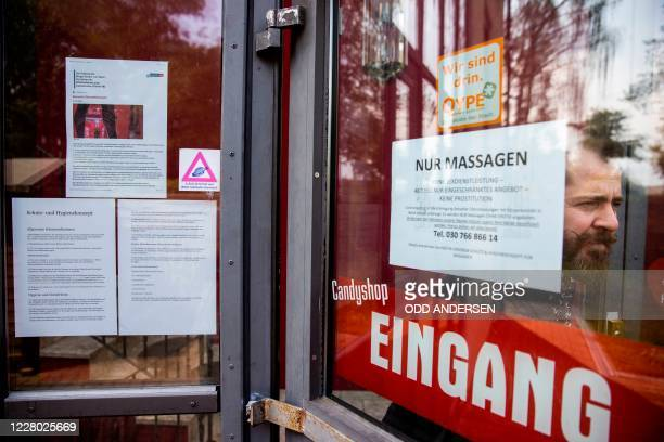 Manager Aurel Johannes Marx is seen at the entrance with notes informing clients the new rules at the Candy Store brothel in Berlin on August 10 2020...