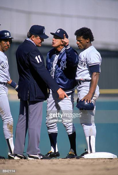 Manager Billy Martin of the New York Yankees argues with an umpire as outfielder Rickey Henderson watches during the game on April 7 1988 at Yankee...