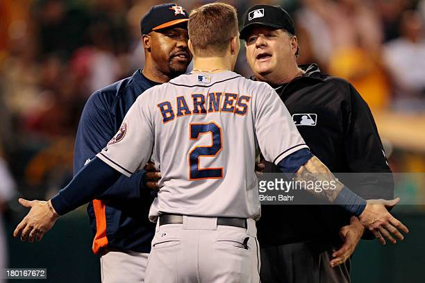 Manager Bo Porter restrains Brandon Barnes of the Houston Astros as he argues with crew chief Jerry Layne after the umpires declined to award Brandon...