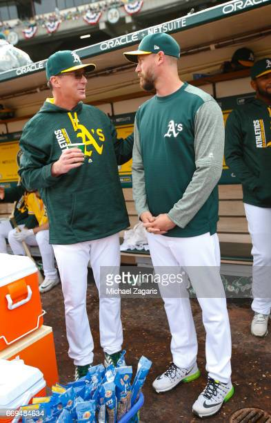 Manager Bob Melvin and John Axford of the Oakland Athletics talk in the dugout during the game against the Los Angeles Angels of Anaheim at the...