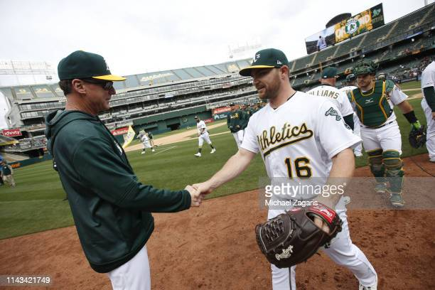 Manager Bob Melvin and Liam Hendriks of the Oakland Athletics celebrate on the field following the game against the Boston Red Sox at the...