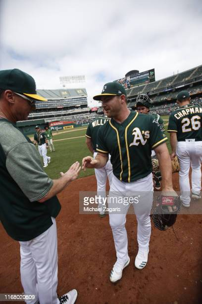 Manager Bob Melvin and Liam Hendriks of the Oakland Athletics celebrate on the field following the game against the Milwaukee Brewers at the...