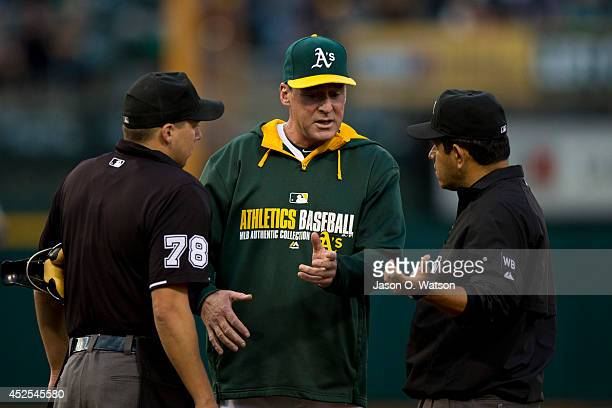 Manager Bob Melvin of the Oakland Athletics argues a call with umpire Adam Hamari and umpire Alfonso Marquez during the third inning against the...