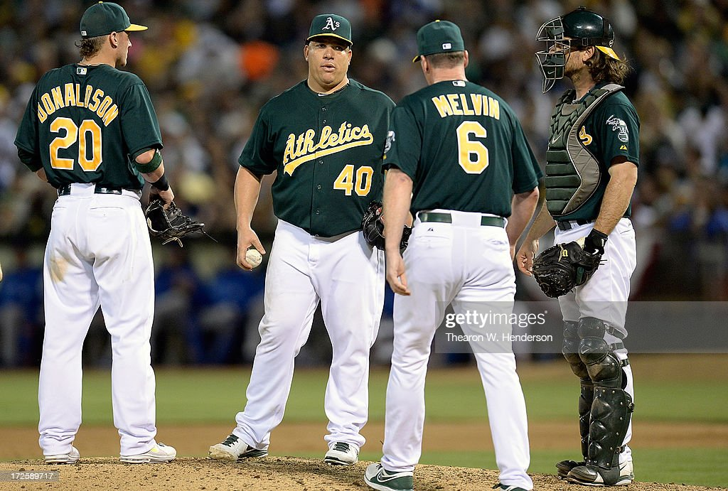 Manager Bob Melvin #6 of the Oakland Athletics comes out to talk with pitcher Bartolo Colon #40 as Josh Donaldson #20 and John Jaso #5 looks on in the seventh inning against the Chicago Cubs at O.co Coliseum on July 3, 2013 in Oakland, California.