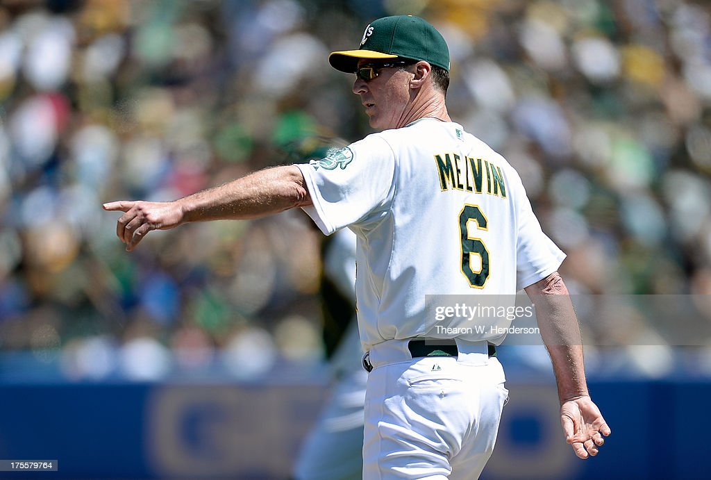 Manager Bob Melvin #6 of the Oakland Athletics signals the bullpen as he walks to the mound to make a pitching change in the seventh inning against the Texas Rangers at O.co Coliseum on August 4, 2013 in Oakland, California.