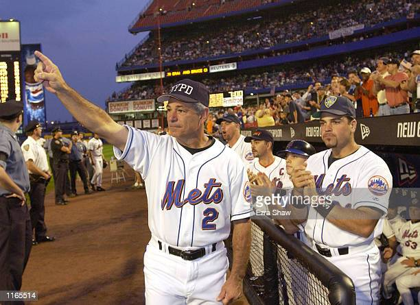 Manager Bobby Valentine and catcher Mike Piazza of the New York Mets applaude in honor of New York City Mayor Rudolph Giuliani before the Mets'' game...