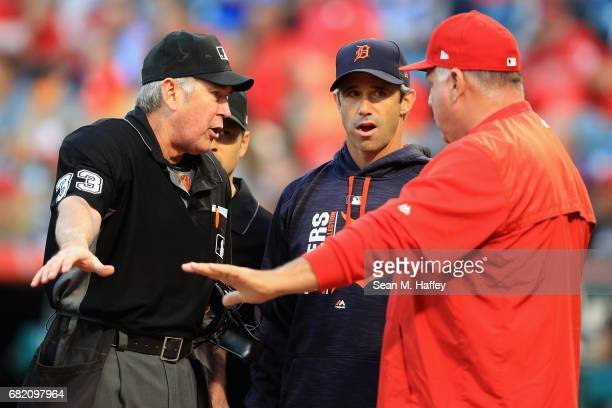 Manager Brad Ausmus of the Detroit Tigers talks with manager Mike Scioscia of the Los Angeles Angels of Anaheim and umpire Mike Winters prior to a...