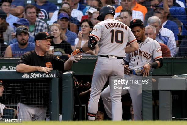 Manager Bruce Bochy and Evan Longoria of the San Francisco Giants celebrate after Longoria hit a home run in the first inning against the Chicago...