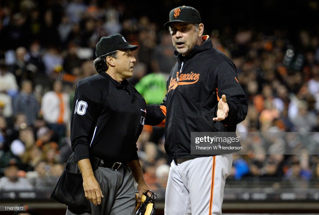 Manager Bruce Bochy #15 of the San Francisco Giants argues with home plate umpire Phil Cuzzi #10 over a safe call for Jay Bruce #32 of the Cincinnati Reds in the fifth inning at AT&T Park on July 23, 2013 in San Francisco, California.