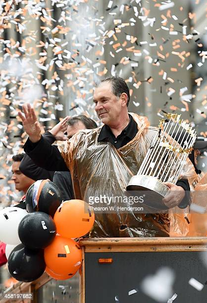 Manager Bruce Bochy of the San Francisco Giants holding the Commissioner's Trophy waves to the crowd along the parade route during the San Francisco...
