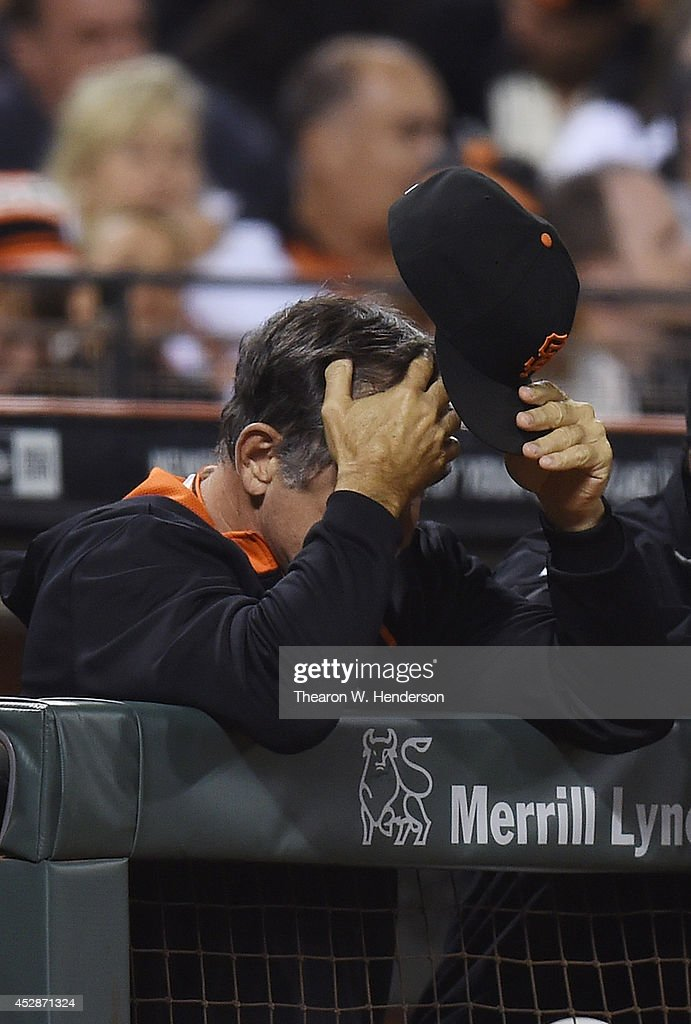 Manager Bruce Bochy #15 of the San Francisco Giants leans over the rail of the dugout, rubbing his forehead while the Giants are down 5 to 0 to the Pittsburgh Pirates in the bottom of the sixth inning at AT&T Park on July 28, 2014 in San Francisco, California.