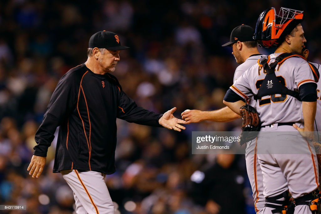 Manager Bruce Bochy takes the baseball from starting pitcher Ty Blach #50 of the San Francisco Giants during the sixth inning as Buster Posey #28 looks on against the Colorado Rockies at Coors Field on September 5, 2017 in Denver, Colorado.