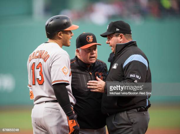 Manager Buck Showalter and Manny Machado of the Baltimore Orioles argue with home plate umpire DJ Rayburn after he warned both benches following an...
