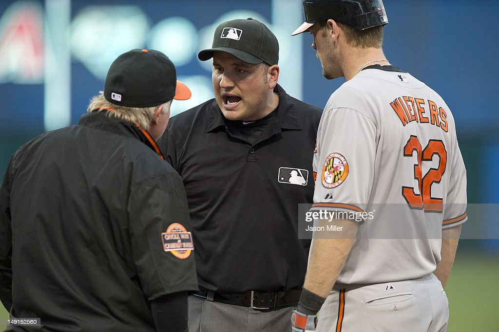 Manager Buck Showalter #26 and Matt Wieters #32 of the Baltimore Orioles argue a call with first base umpire Dan Bellino #2 during the seventh inning against the Cleveland Indians at Progressive Field on July 23, 2012 in Cleveland, Ohio.